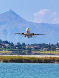Airplane taking off from Corfu town airport. View from the sea royalty free stock photography