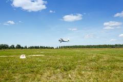 An airplane taking off from grass fields. The plane takes off from field Royalty Free Stock Photos