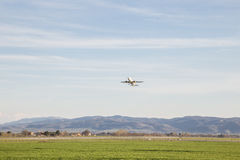 Airplane taking off. An airplane taking off from a little airport, with a big sky and green meadows stock images