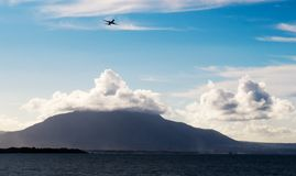 Airplane taking off | Mount Isabel de Torres. An airplane taking off with Mount Isabel de Torres in the background and an ocean cove in Puerto Plata, Dominican royalty free stock photos