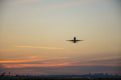 Airplane is taking off during sunrise. Stock Photos