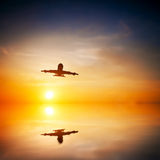 Airplane taking off at sunset stock image