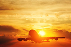 Airplane taking off at sunset Stock Photos