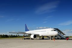 Airplane on tarmac. Commercial airliner parked in a tropical airport on the tarmac and loading cargo with boarding passengers under an azure blue sky royalty free stock photography