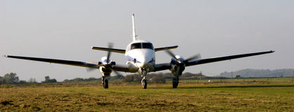 Airplane taxiing. Aircraft taxiing in grassy airfield royalty free stock images