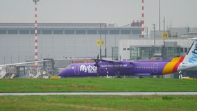 Airplane taxiing after landing. DUSSELDORF, GERMANY - JULY 24, 2017: FlyBe Bombardier DASH 8 Q400 G-PRPE taxiing after landing at rain. Dusseldorf airport stock video