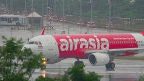 Airplane taxiing Phuket airport at rain. PHUKET, THAILAND - DECEMBER 2, 2016: Airbus 320 AirAsia HS-BBH turn runway before departure on wet runway of Phuket stock video footage