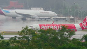 Airplane taxiing Phuket airport at rain. PHUKET, THAILAND - DECEMBER 2, 2016: Airbus 320 AirAsia HS-BBH turn runway before departure on wet runway of Phuket stock video