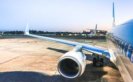 Airplane at terminal gate ready for takeoff at blue hour - Modern international airport with boarding aircraft on nighttime - royalty free stock photo