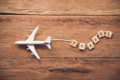Airplane with the text. `Travel` placed on a wooden floor. Travel ideas royalty free stock photo