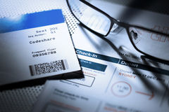 Airplane Ticket Boarding Pass. A still life with an airline boarding pass and itinerary with a pair of reading glasses Stock Photo