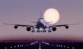 Airplane touch down during sunset Stock Photos