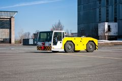 Aircraft tow tractor moves beside to the hangars. Airplane tow tractor moves beside to the hangars royalty free stock images