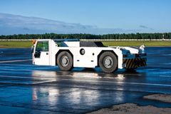 Airplane tow tractor at the airport apron. Airplane tow truck at the airport apron royalty free stock photography