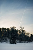 Airplane track on sunset sky, winter scene on foreground Stock Image