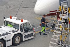 Airplane tractor airport germany berlin tegel. Ramp service for airplane dispatching, airplane check before the next takeoff stock images