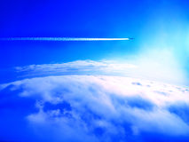 Airplane trail above the clouds Royalty Free Stock Image
