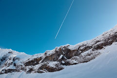 Airplane Trail above Mountain Peak Royalty Free Stock Photography
