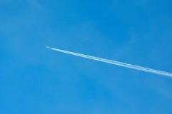 Airplane trail across the blue sky Royalty Free Stock Photography