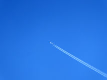 Airplane trail. On a bright blue sky Stock Image