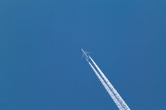 Airplane trail in the sky. An airplane and its big trail on the blue sky royalty free stock photos