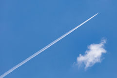 Airplane trail speed through cleared blue sky. Royalty Free Stock Images