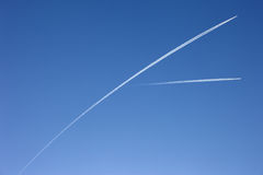Airplane trails across a pure blue sky Royalty Free Stock Images