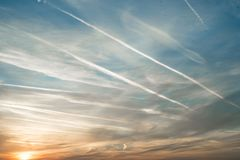 Airplane trails over a blue sky at sunset royalty free stock photography