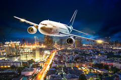 Airplane over night scene city. Airplane for transportation flying over the night scene cityscape Royalty Free Stock Photos