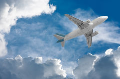 Airplane travel. Airplane flying through clouds towards the sun Stock Photography