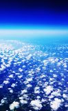 Airplane Travel View From a Window of Sky, Clouds and Farm Land Stock Photo