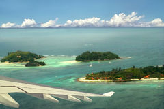 Airplane is turning above tropical islands. Royalty Free Stock Photography