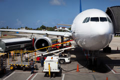 Airplane Unloading the Luggages at the Airport Royalty Free Stock Image