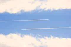 Airplane vapour contrails against vivid blue sky Royalty Free Stock Image