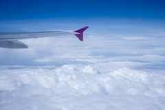 Airplane view above the clouds. In a suuny day royalty free stock photo