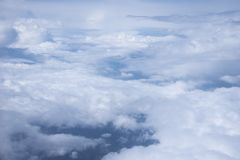 Airplane view above the clouds. In a suuny day royalty free stock images
