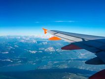 Airplane view of mountains and lake. Beautiful aerial view of summer Alps mountains and lake with blue sky from airplane window royalty free stock photography