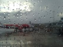 Airplane view on a rainy day. View of an airplane through window with raindrops royalty free stock photography