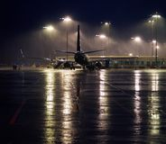 An airplane waiting in the darkness. An airplaine waits for the flight on a wet and rainy evening stock photos