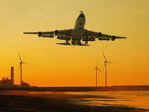 Airplane and wind power generator. And sunset Royalty Free Stock Photos