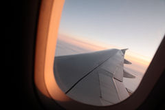Airplane Window. Photograph of a sunset/sunrise view through an airplane window. The free space in the sky could be utilized as copy space royalty free stock photos