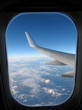 Airplane window. With a view of wing, sky and clouds Royalty Free Stock Images