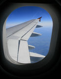Airplane window. Looking out over the wing Stock Photography