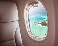 Airplane window with beautiful Maldives island view. Airplane interior with window view of Maldives island. Concept of travel and air transportation stock image