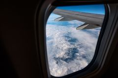 Airplane window from inside. Through the window you can see clouds and airplane wing. Stock Photo