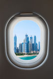 Airplane window from interior of aircraft with modern city view. Stock Photos