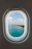 Airplane window from interior of aircraft and tropical beach. Stock Photos