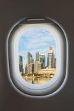 Airplane window and modern city skyline. Royalty Free Stock Photos
