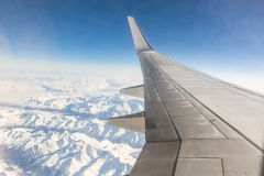 Airplane window seat view while flying over snowy mountains Royalty Free Stock Images