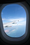 Airplane window view. Cloudy blue sky looking through airplane window Stock Image